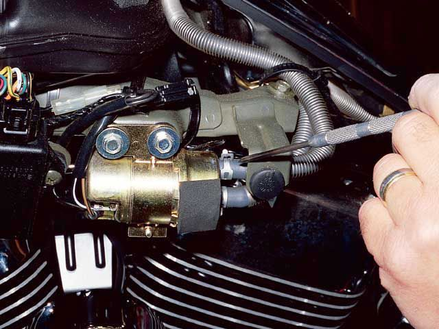 To check fuel flow when a remote tank/pump is used, locate the fuel pump. This one is located under the side cover. Remove the discharge side hose—that's the one from the pump to the carburetor.